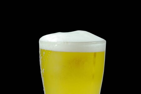 cold beer with frothy in glass on black background