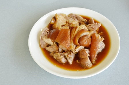 Braised pork leg with black Chinese herb soup slice on plate