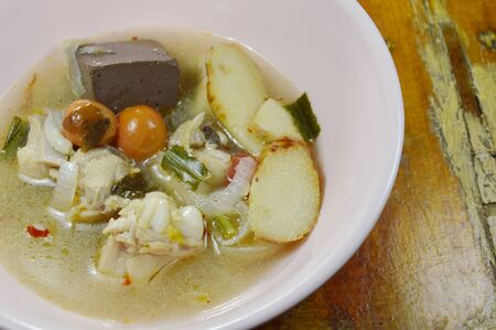 boiled chicken in hot and spicy tom yum soup on bowl