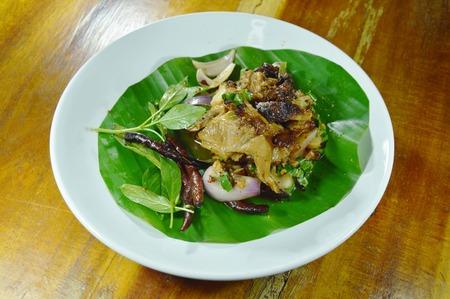 Thai spicy slice roasted pork salad on banana leaf