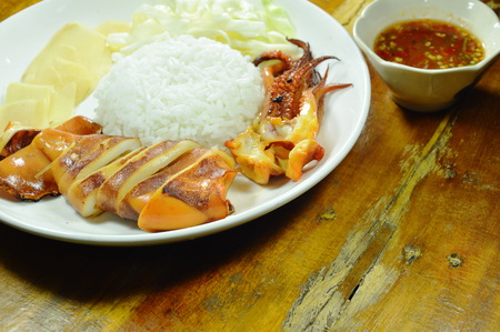 grilled squid with rice topping slice cabbage and ginger on plate Stock Photo