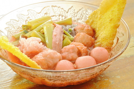 Boiled fish and shrimp ball topping pickled squid in red soybean sauce soup on bowl 스톡 콘텐츠