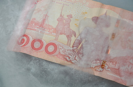 Thai banknote freezing in ice on plastic tray