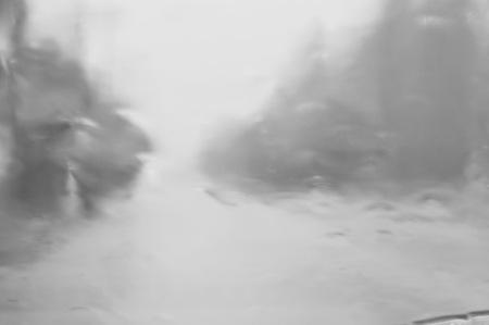 blurry of heavy rain falling through car windshield