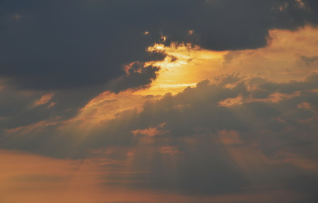 sunlight spreading through dark cloud in evening