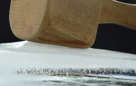 big and heavy wooden hammer smashed ice brick on black background