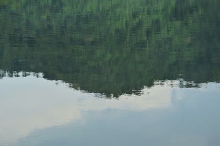blurry mountain reflection on water surface in lake 免版税图像
