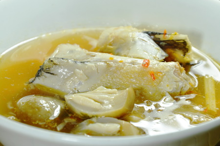 salmon fish head and straw mushroom in tom yum soup on bowl