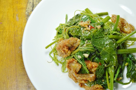 fried Chayote sprout with crispy chicken on plate