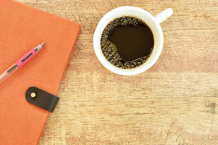 diary book and pen with black coffee cup on wooden table 写真素材