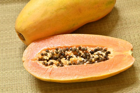 ripe papaya tropical fruit half cut on bamboo mat