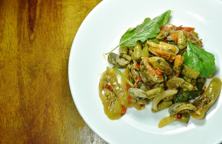spicy stir fried mussel with basil leaf on plate