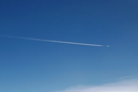 airplane flying make condensation tail on sky in sunshine day