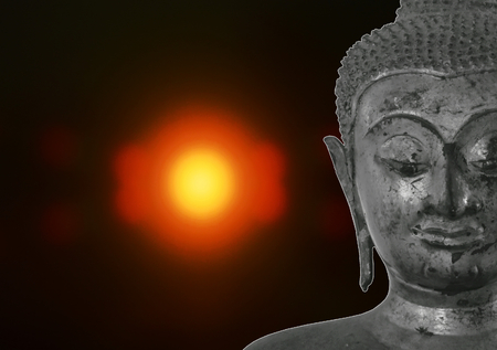 ancient Buddha image on blurry candle light in dark background