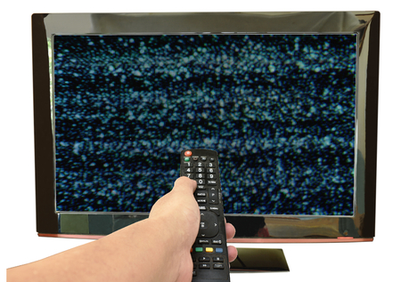 hand holding television remote control pointing to glitch on screen background