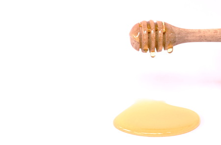 honey on wooden scoop in white background