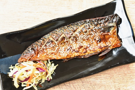grilled Saba fish or mackerel with sweet black soy sauce topping white sesame on plate