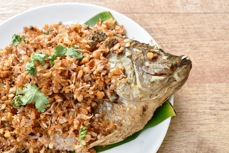 Batter fried mango fish topping chop garlic on banana leaf