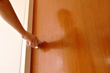 hand twisting silver knob to opened wooden door in home