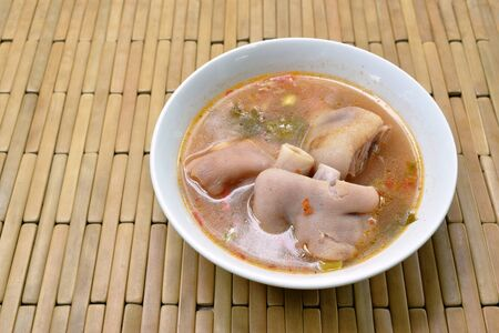 boiled spicy pork knuckle in tom yum soup on bowl
