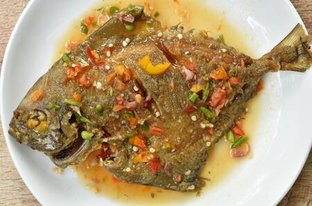 deep fried white pomfret dressing spicy sauce on plate