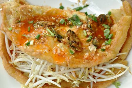 fried egg stuffed mussel with bean sprout topping garlic and dressing chili sauce on plate Фото со стока