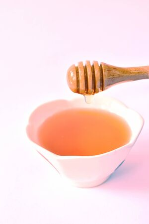 honey on wooden scoop drop to cup in white background Stock Photo