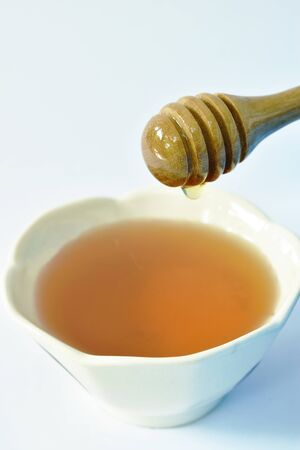 honey on wooden scoop drop to cup in white background Stock fotó
