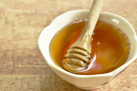 honey and wooden scoop in cup on table Stock Photo