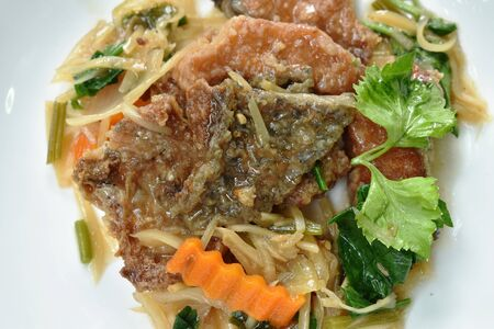deep fried chop fish with slice ginger and celery on plate