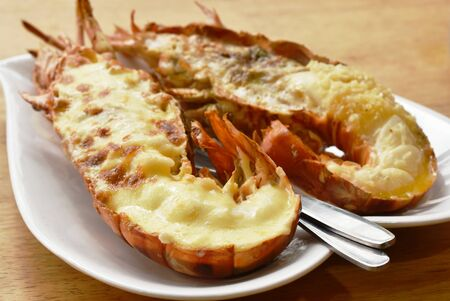grilled lobster shrimp with cheese and butter garlic on plate Stock Photo