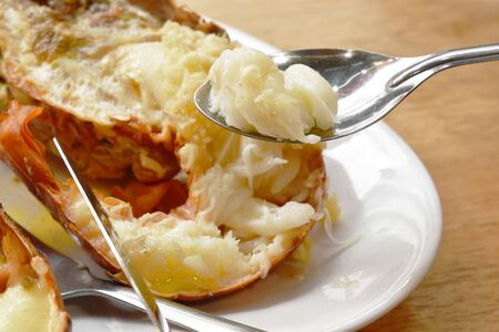 grilled lobster shrimp with cheese and butter garlic scooping by silver spoon on plate