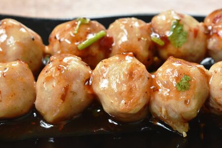 grilled pork tendon meat ball stabbing in wooden stick dressing spicy and sweet sauce on plate