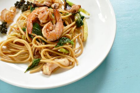 spicy stir fried spaghetti seafood with pepper and basil leaf on plate