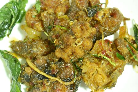 spicy stir fried crispy catfish curry with herb on plate Banco de Imagens