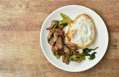 spicy stir fried slice grilled pork with chili and basil leaf topping egg on dish