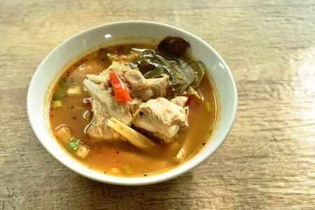hot and spicy pork bone with tamarind and Thai herbs soup on bowl Фото со стока
