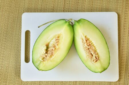 Japanese green melon cutting on white plastic cutting board Фото со стока