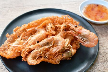 deep fried shrimp with flour on dish dipping with sweet chili sauce