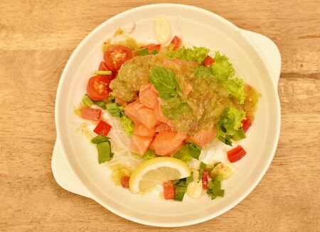 fresh salmon with vegetable spicy sauce salad on plate