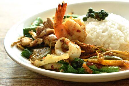 pesce saltato in padella piccante e carne con peperoncino su riso