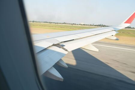 plane wing while take off from airport runway through window frame
