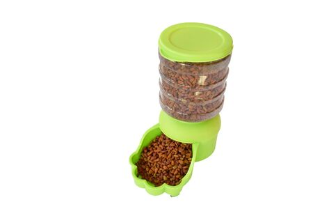 dry pet food in green automatic pet feeder for dog and cat on white background