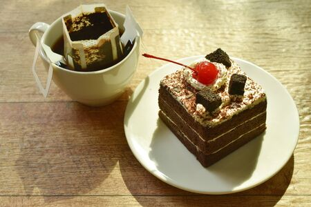 black fotest cake with cream topping cherry and hot coffee drip filter in cup