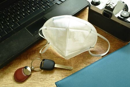 hygienic mask in front of laptop and film camera with car key on table for travel