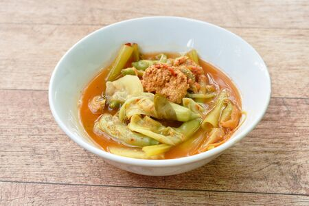 boiled mixed vegetable and fish egg in Thai spicy soup on bowl Stockfoto