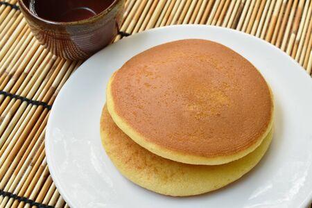 Dorayaki Japanese pancake stuffed sweet mashed bean on plate eat with tea cup