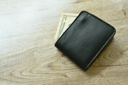 ten US dollar banknote from wallet on table