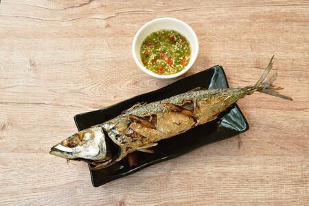 deep  fried saba fish or mackerel on plate dipping spicy sauce