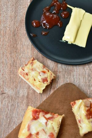 piece of pizza topping sausage and cheese on wooden cutting board Stock fotó